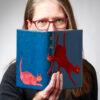 Katarina Persson går tredje året på bokbinderilinjen på Leksands Folkhögskola. Boken hon håller i är Maria Langs De röda kattorna, helskinnband i fransk teknik med mockapåläggningar. Du hittar Katarina på www.bokateljen.se eller e-post kp@bokateljen.se