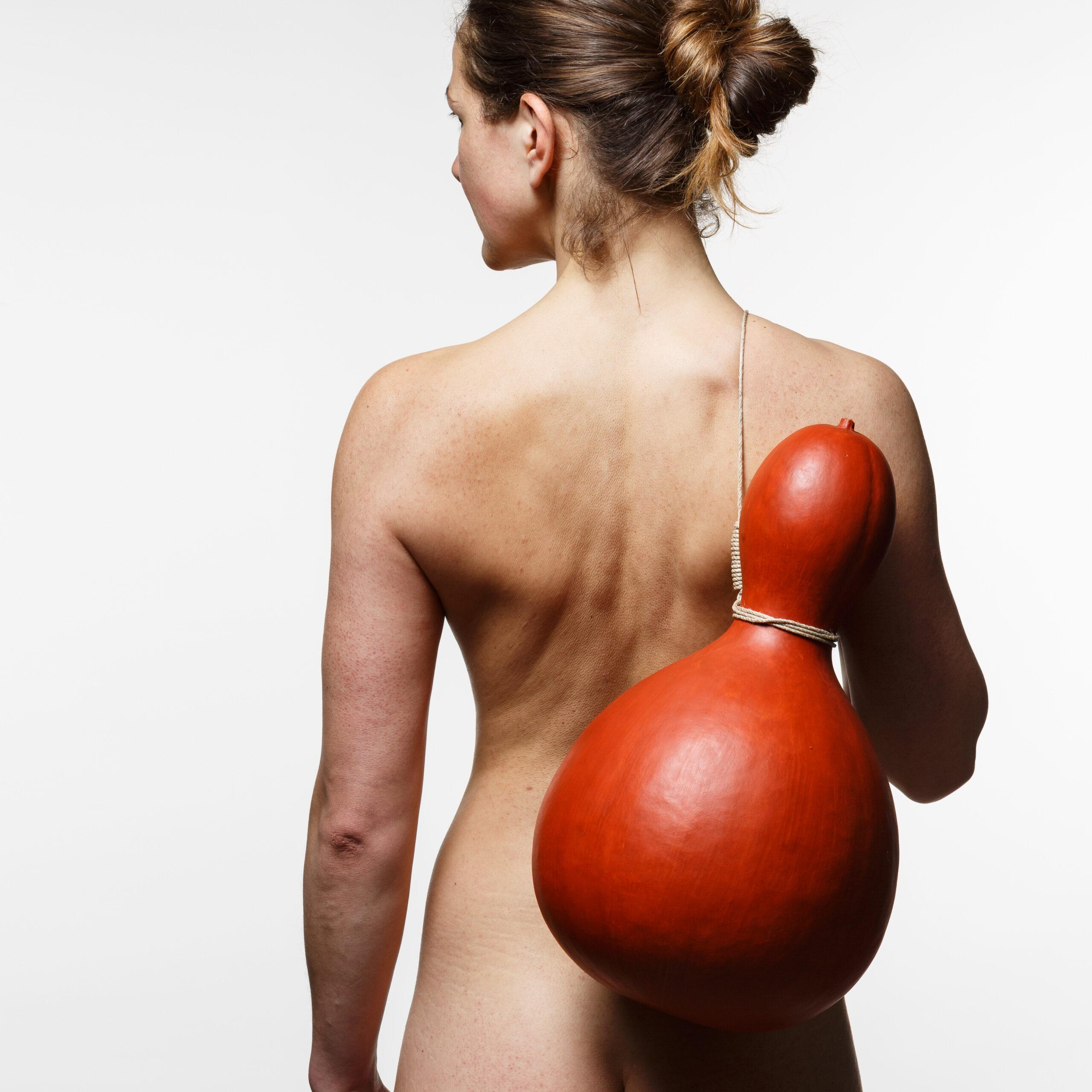 Naken kvinna med en kalebass hängande över axeln i en snara.