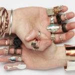 Två händer med många smycken. Annonsbild till elevutställning för Leksands folkhögskola Metall. Foto: Christian Habetzeder.