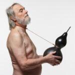 Naken man som håller en kalebass i händerna sammankopplade med en snara.
